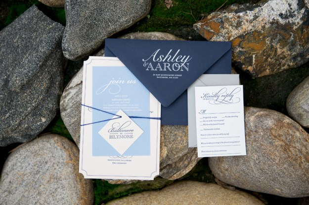 Navy and light blue wedding invitation stationery suite arranged on rocks.