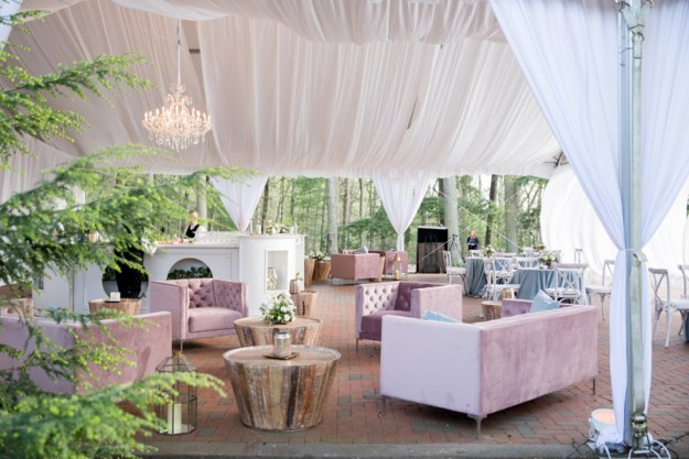 Pink and white wedding reception seating area beneath a tent draped with fabric