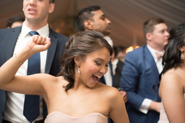 Girl dancing and smiling with arms raised on a crowded dance floor.