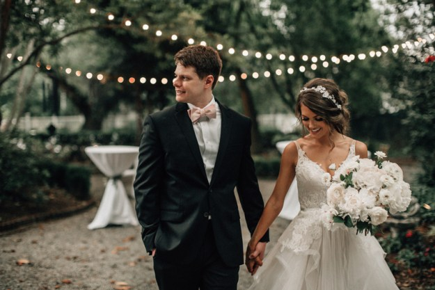 Bride and groom holding hands with string lights in background