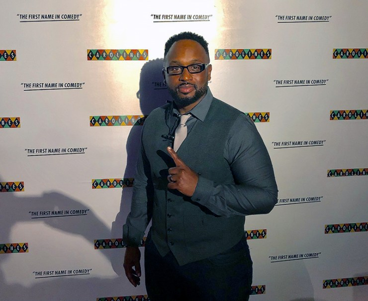 Comedian Will Jacob standing in front of step and repeat at Caroline's on Broadway