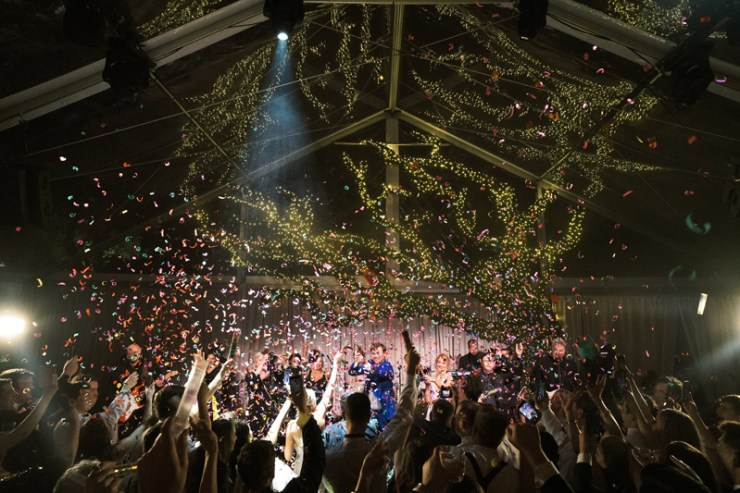 Tented wedding reception with crowded dance floor and confetti cannons.