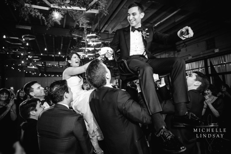 Bride and groom lifted in chairs during reception to sounds of Modern Luxe wedding band.