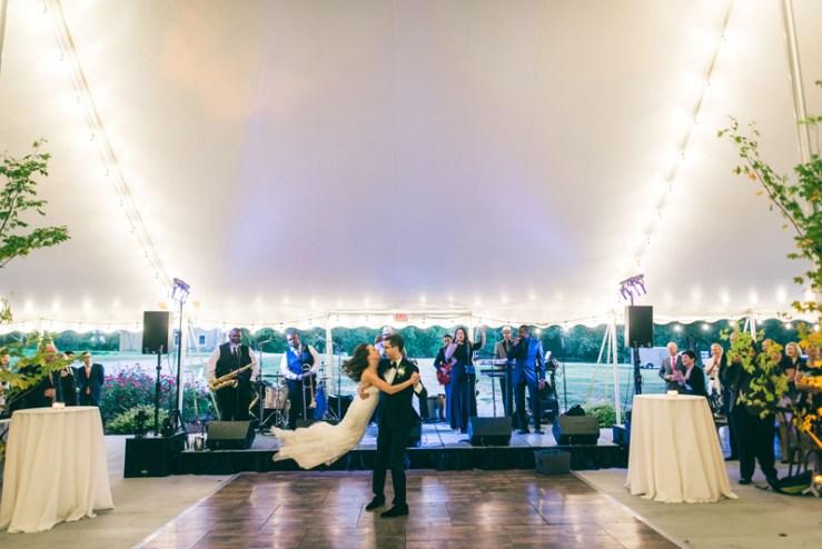 Groom swinging bride on dance floor during Summerfield Farms wedding reception.
