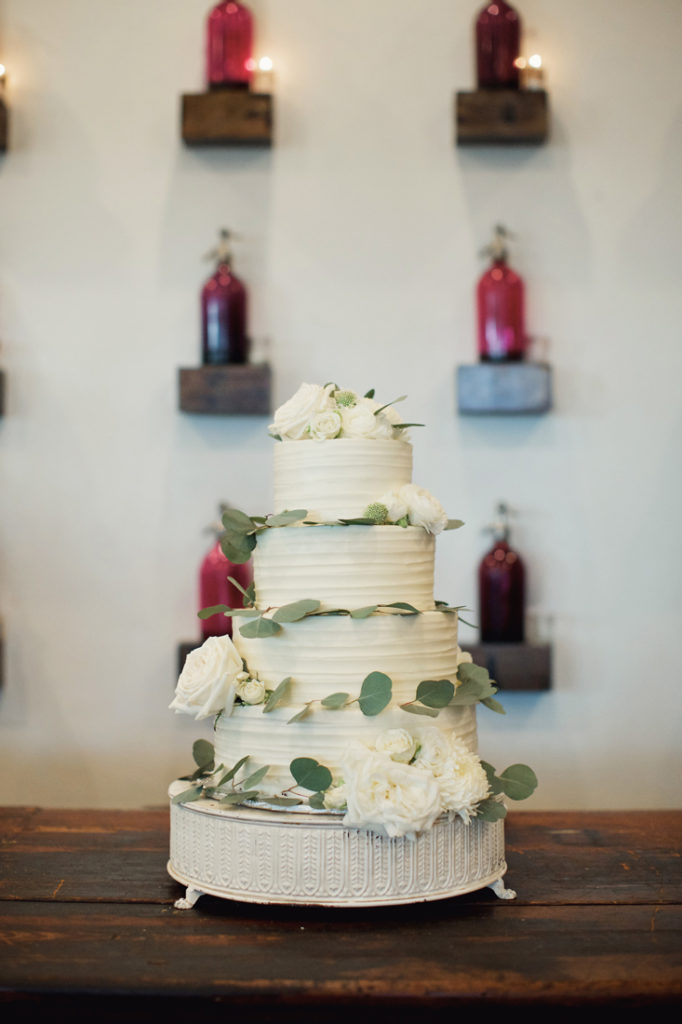 Four tier wedding cake with white flowers and greenery.
