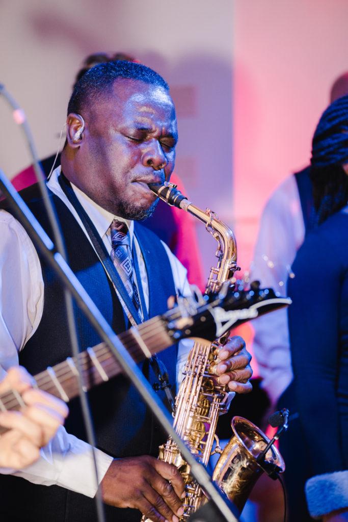 Sax player performing at Bride and groom dancing The Hora at Jewish wedding at Chesapeake Bay Beach Club wedding reception.