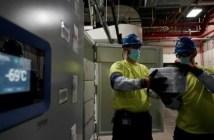 موظفان في شركة فايزر ينقلان صندوقا من اللقاح في كالامازو