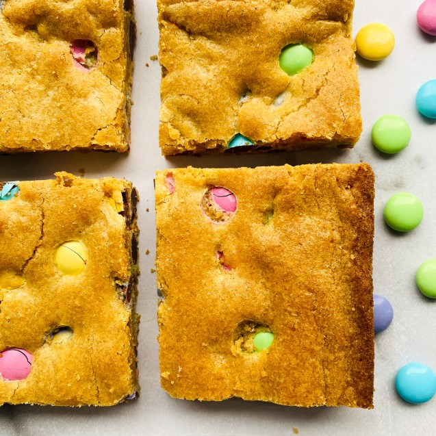 Close up of 4 of the easiest easter blondies against a white background and easter m&m's sprinkled on the background.