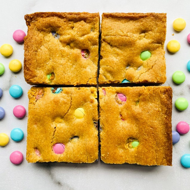 4 of the easiest easter blondies against a white background and easter m&m's sprinkled on the background.
