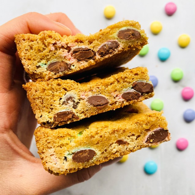 Hand holding up 4 of the easiest easter blondies against a white background and easter m&m's sprinkled on the background.