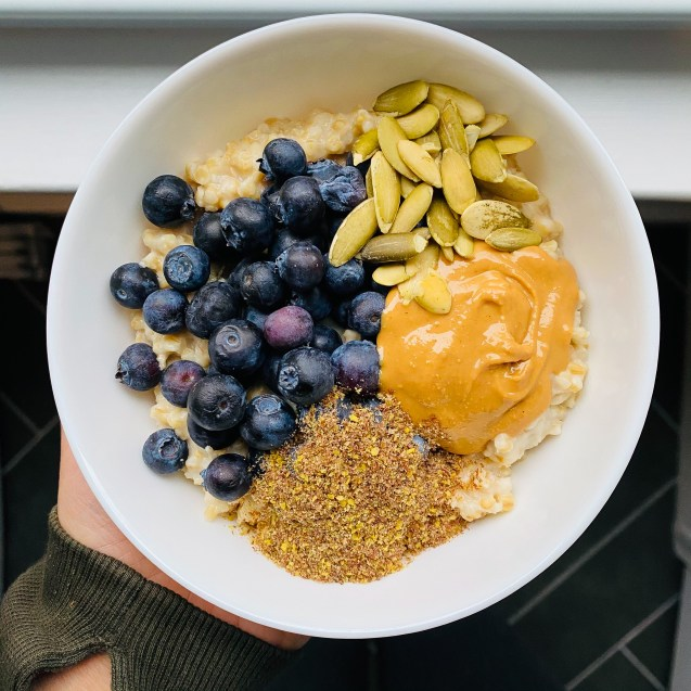 Crockpot steel cut oats in a white bowl topped with blueberries, cashew butter, pumpkin seeds, and flaxseeds with a hand holding against a dark background.