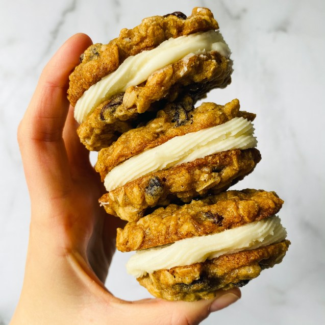 Hand holding up three oatmeal raisin whoopie pie cookies stacked against a white background.