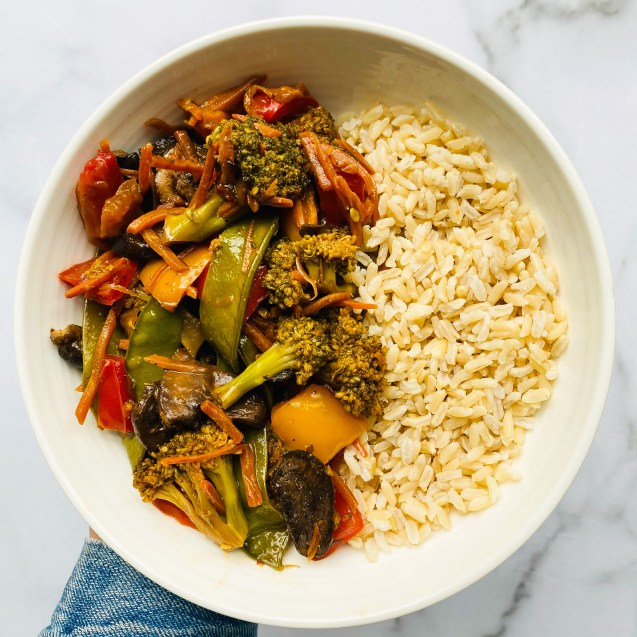 Photo of veggie stir fry with brown rice in a white bowl against a white marble background and hand holding bowl.