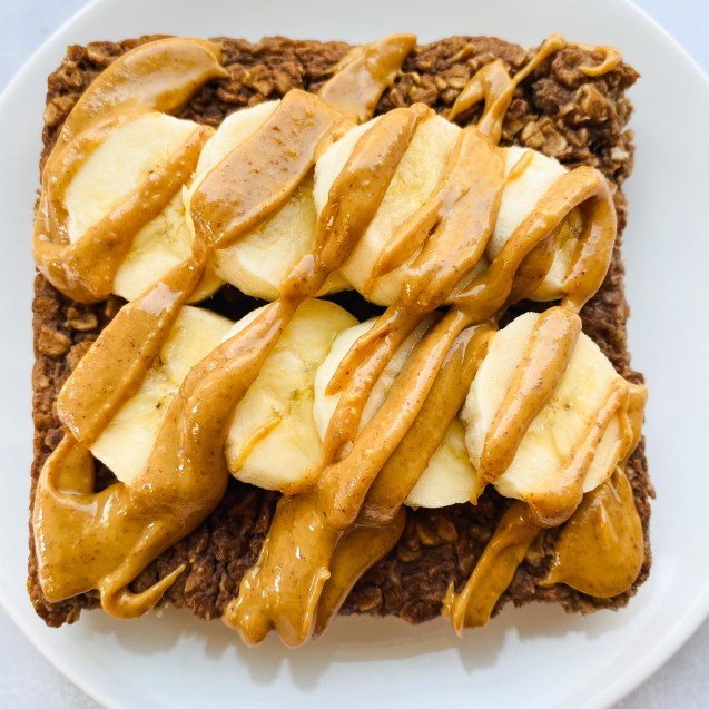 Close up of a slice of chocolate protein baked oatmeal with bananas on top and drizzled with peanut butter on a white background.