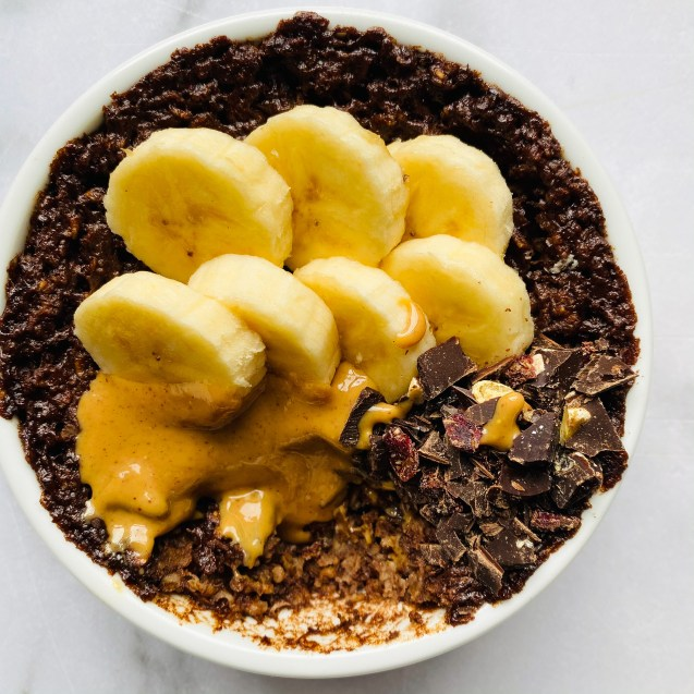 Close up photo of brownie baked oatmeal in a white ramekin on a white background and topped with banana slices, peanut butter, and chopped chocolate with a bite missing from the bottom.