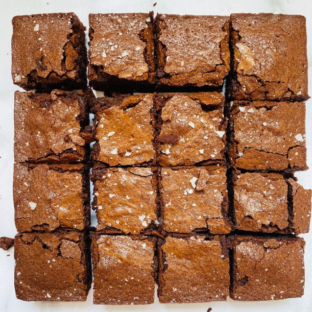 A overhead photo of the fudgy homemade brownies cut into 16 squares, sprinkled with sea salt, against a white background.