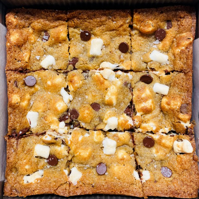 Close up of pan of s'mores cookie bars cut into 9 pieces.