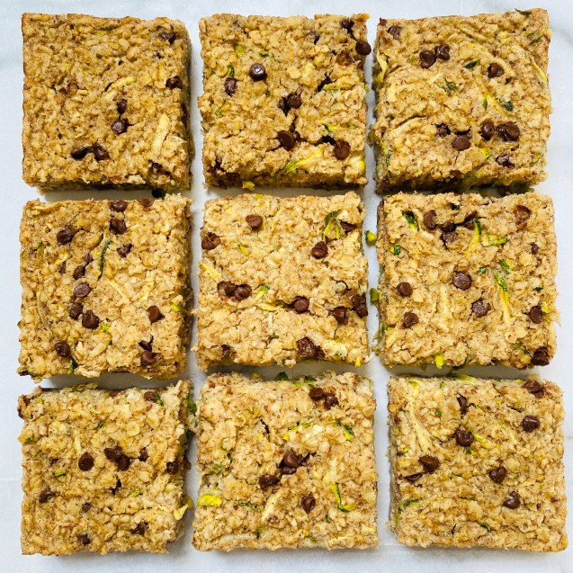 Photo of close up of 9 squares of chocolate chip zucchini baked oatmeal on a white background.