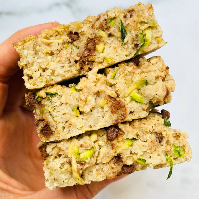 Photo of close up of 3 squares of chocolate chip zucchini baked oatmeal stacked on top of another with a hand holding on a white background.