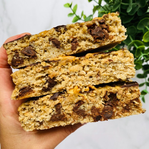 Three slices of peanut butter cup baked oatmeal stacked on top of each other with a hand holding and a green plant in top right.