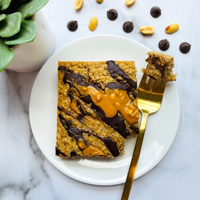 Slice of peanut butter cup baked oatmeal on a white plate against a marble background with a bite on a gold fork. A green plant in the top left and peanuts and chocolate chips in the top right.