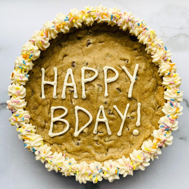 Close up of the chocolate chip cookie cake with white icing around the sides, sprinkles, and happy bday! in the middle against a white background.