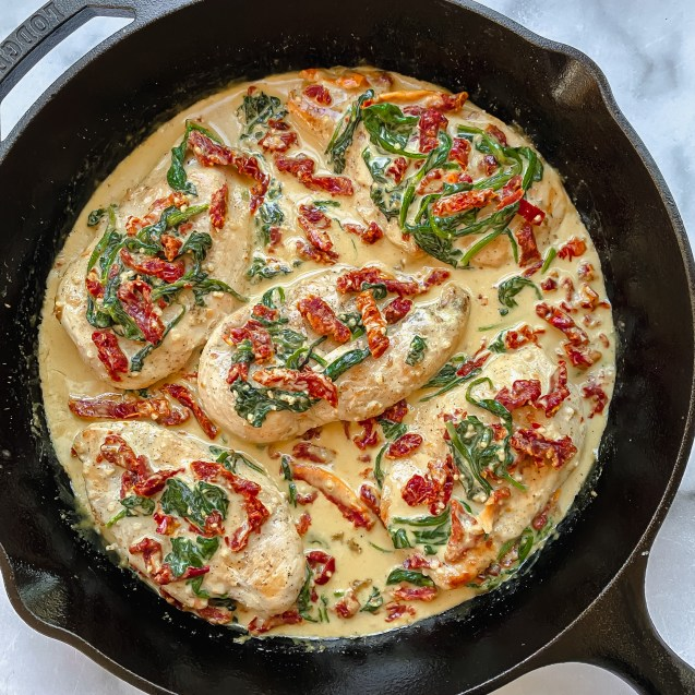 Top view of creamy tuscan skillet chicken in a cast iron with creamy sauce topped with spinach and sundried tomatoes.