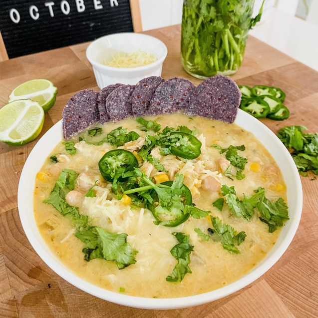 A white bowl filled with creamy white chicken chili and topped with cheese, jalapeno, cilantro, and chips with lime, jalapeno and cilantro in the background on a wooden cutting board.