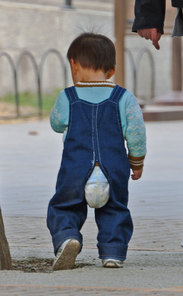 A toddler boy with pull up poking out of pants