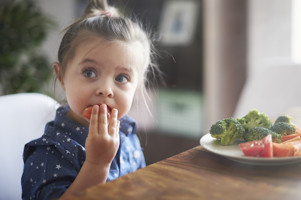 Little girl eating vegetables at table