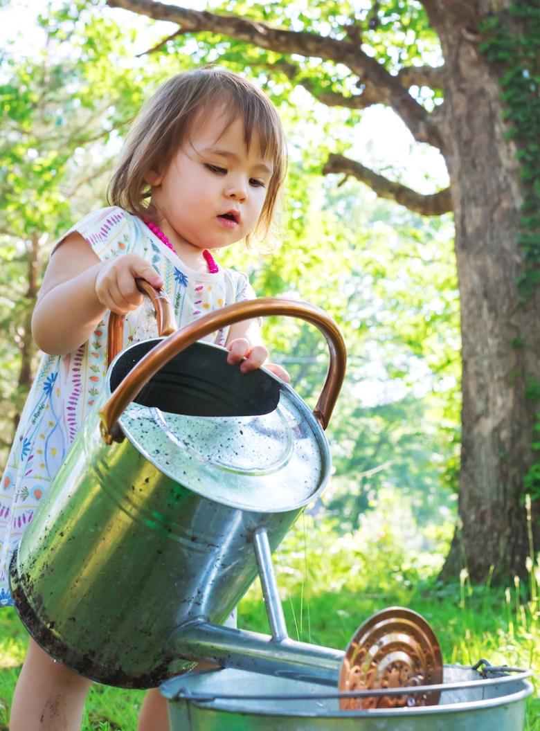 Toddler girl named Natalie watering flowers