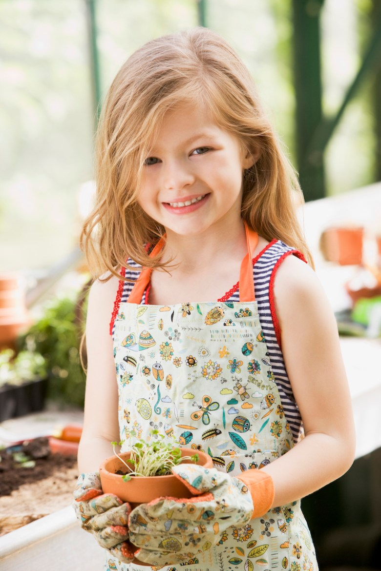 Young girl named Piper posing in garden greenhouse