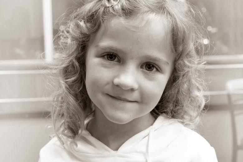 Little girl named Savannah smiling in black and white