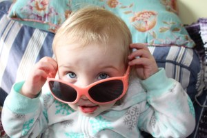 toddler looking over top of sunglasses