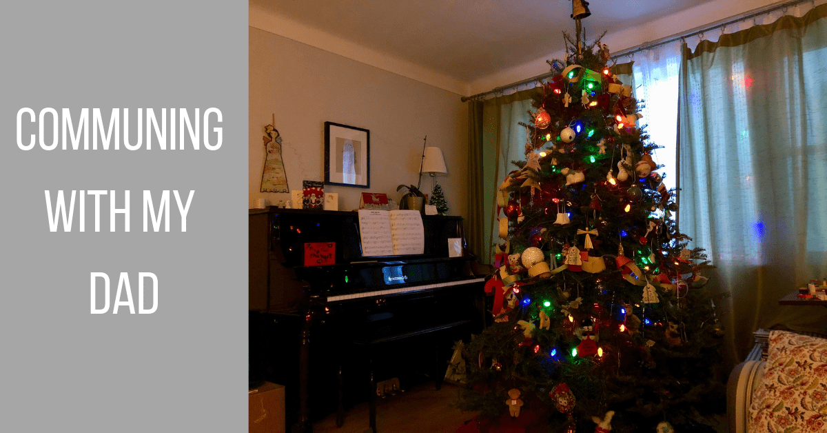 Image of a lit Christmas tree beside a piano in a living room