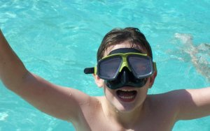 Boy wearing goggles, swimming pool