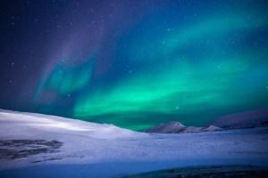 Northern lights, snowy ground. Stars.