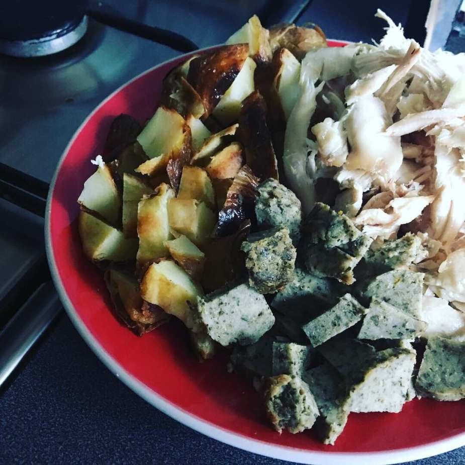 chopped chicken, roast potato and stuffing on red plate