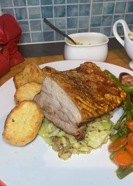 Roast Pork on a bed of mustard cabbage, with ginger and orange glazed carrots, steamed ve and roast potatoes. With apple sauce and gravy