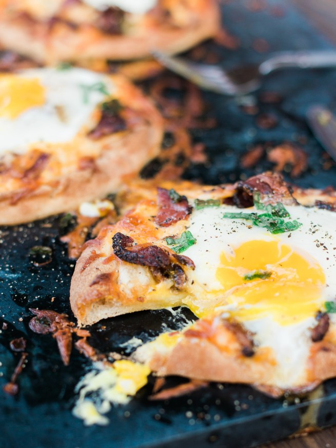 Breakfast pizza using Naan bread, loaded with cheese, bacon and topped with an egg! Hits the spot every morning!!