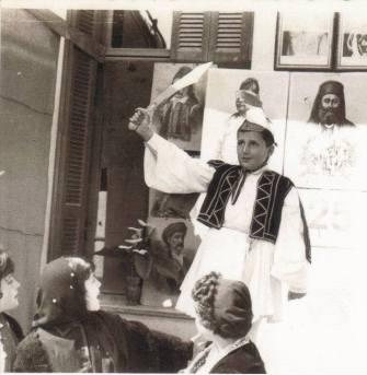 1962 Εορτή 25ης Μαρτίου στο 1ο Δημ. Σχολείο. Ο μαθητής της Ε΄ Δημοτικού Γιώργος Πισιμίσης, με φουστανέλα και σπαθί, αναπαριστά τον Θ. Κολοκοτρώνη. Οι κοπέλες μπροστά του είναι οι μαθήτριες της Ε τάξης (από αριστερά) Γεωργίου, Νοδάρου, Δουλβίτσου (Φωτο : Αρχείο Γ. Πισιμίση)