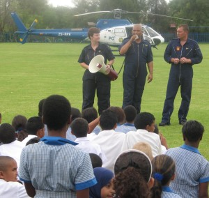 Const Whiteley, Capt Cloete (pilot) addressing the learners and Sgt Mark Douglas with the Squirrel helicopter used to spray dagga plantations