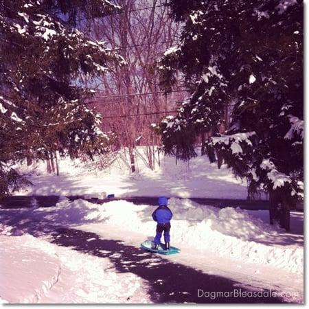 boy sledding down a driveway, standing on sled