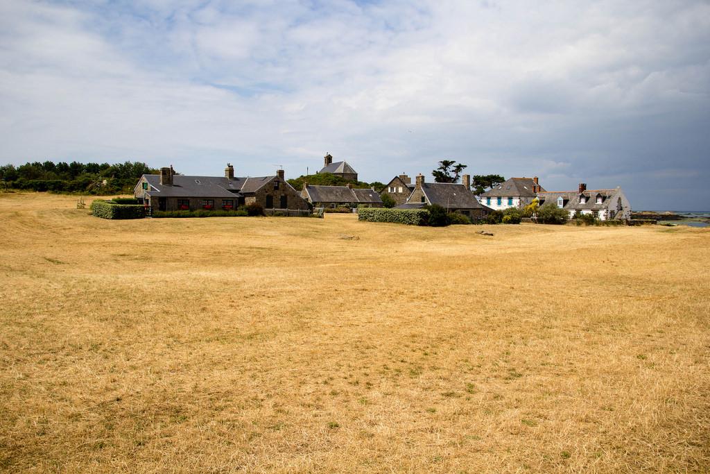 Beau champ de blé coupé, et le village au fond.