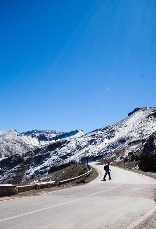Passant traversant la route, devant des sommets enneigés.