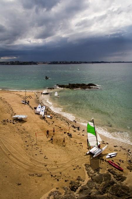 Optimistes et catamaran, sur la plage.
