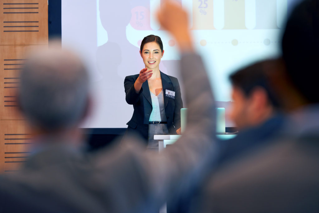 A portrait of a businesswoman gesturing while giving a presentation at a press conference