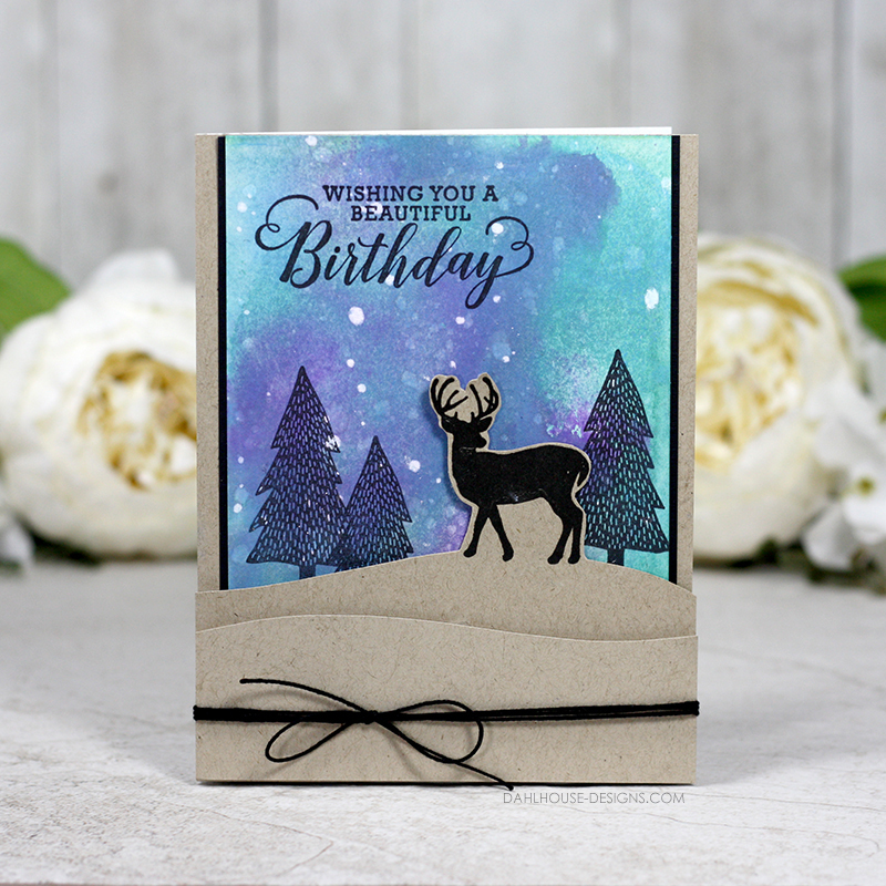 Sharing a card using Distress Oxide Inks to create a Winter Sky background. The soft cool colors with some flecks of falling snow are the perfect backdrop for the sweet deer and trees in this birthday card. It has a great layout and would be great as a masculine card as well. More inspiration at dahlhouse-designs.com. #cardmaking #stamping #ideas #diy #howto #tutorial #video #handmade #dahlhousedesigns #unitystampco #distressink #oxides #masculine #birthday