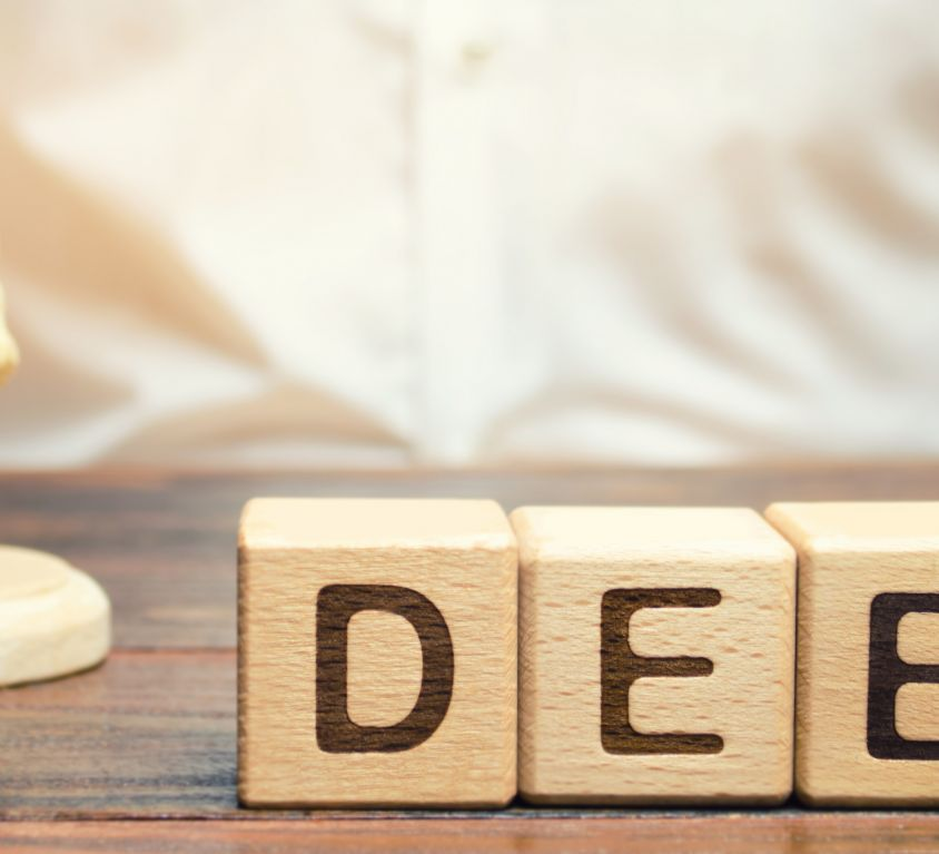 Wooden blocks with the word Debt and judge with a gavel. The concept of judicial punishment for non-payment of debt. Property debts. Tax evasion / avoidance. Bankruptcy and financial crisis