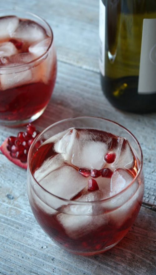 The Pomegranate Fizz is a wine cocktail that is festive and perfect for the holidays. Add this bright red cocktail to your holiday bar menu.